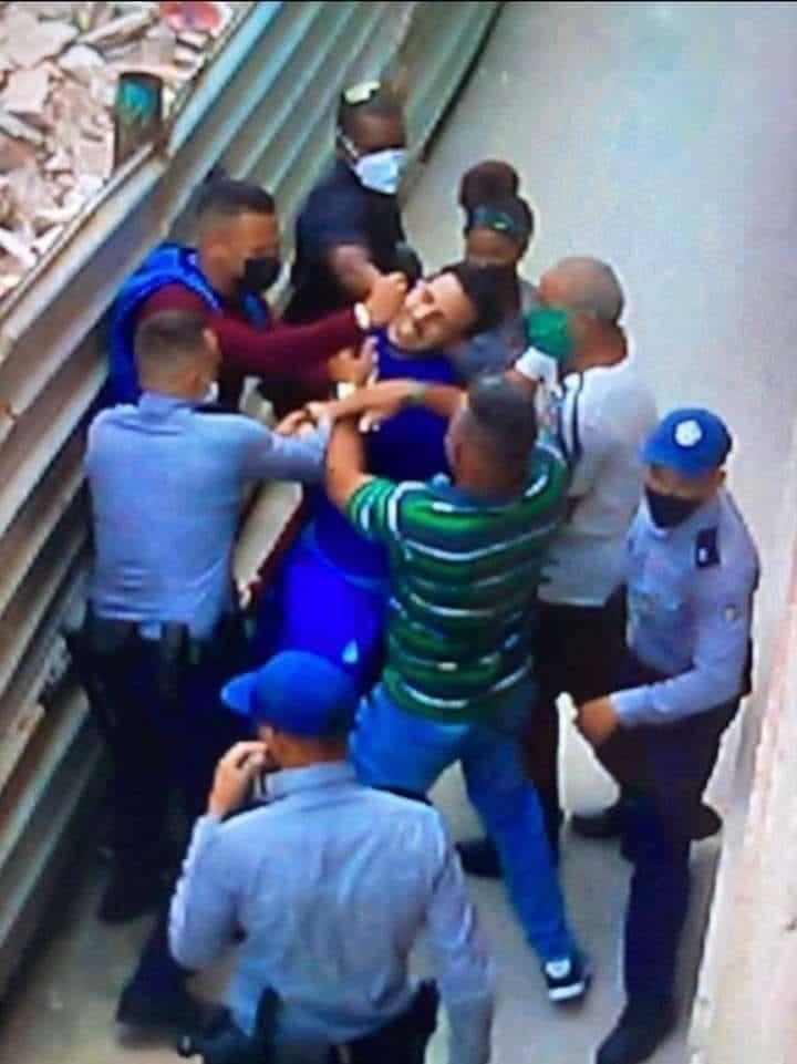 UN joven en la Habana recibe golpes, mientras la policía observa.